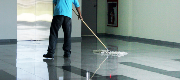 Photo of man in blue shirt and black pants cleaning a shiny hospital floor with a mop